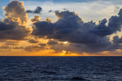 Sunrise in the ocean with clouds. Sunrise in ocean horizon with sky with clouds around sky Stock Images