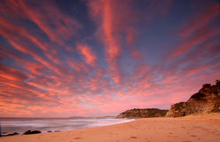 Sunrise ocean scene. Pink glowing clouds at sunrise over the shoreline stock photography