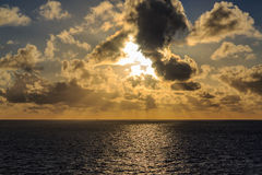 Sunrise in ocean and sun rays. Sun among clouds with sun rays after the sunrise in ocean Royalty Free Stock Photos