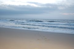 Sunrise on the ocean, white sky, and sand. A beach early in the morning just before sunrise. The sky is a medium blue with a hint of white. The ocean waves are royalty free stock photography