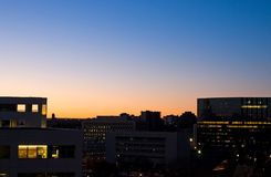 Sunrise and Office Buildings. Daylight breaks over the city and nearby office buildings in this cloudless sunrise view Royalty Free Stock Photo
