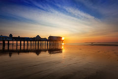 Sunrise at Old Orchard Beach. Sun rises over the wet sands and pier, Old Orchard Beach Maine Royalty Free Stock Photos