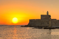 The sunrise at the old port of Rhodes, Greece. The sunrise at the entrance with the deers of the old port of Rhodes, Greece stock photo