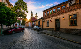 Sunrise in old town. Peaceful sunrise in old european town. sun above the roofs on empty street to Cathedral Stock Photo