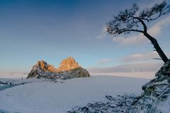 View of the Shamanka Rock and the frozen Lake Baikal during sunrise