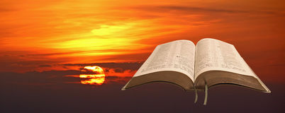 Sunrise open bible. Photo of open bible with sunrise through clouds Royalty Free Stock Image