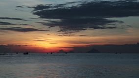 Sunrise orange cloudy sky Vietnam time lapse movie clip. A fiery orange sunrise sky looking out over the south China sea in Nha Trang Bay Vietnam. With fishing stock video
