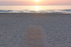 Sunrise in orange hues over the calm sea and pathway leading to the water edge. Sunrise over the sea with reflections royalty free stock image