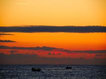 Sunrise with orange and yellow sky. Sunrise with an orange blood sky with fishing boats on the horizon, horizontal clouds, airplane trail Royalty Free Stock Photo