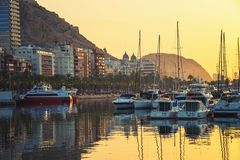 Sunrise over the Alicante harbor, Costa Blanca, Spain. Popular mediterranean summer resort. Yachts and hotels at the background with famous mountains in the Stock Photo