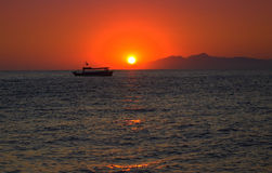 Boat and sunrise over Anafi island,Greece Stock Photos