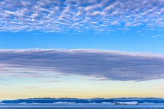 Beautiful morning sky in Greenland over arctic sea and icebergs near Ilulissat stock photography