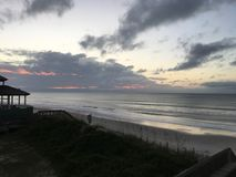 Sunrise over the Atlantic Ocean Coastline, North Carolina. Sunrise with clouds and ocean waves in front of a beachhouse off the Atlantic coast of Topsail Island Stock Photo