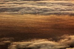 The sunrise over the Atlantic Ocean seen from Pico Volcano. Clouds formation at sunrise over the Atlantic Ocean, seen from Pico volcano 2351m, Pico Island Royalty Free Stock Images
