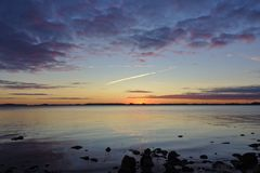 Sunrise over the Baltic Sea with rocks in the foreground Stock Photography