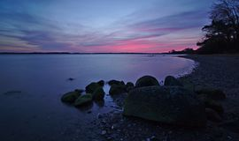 Sunrise over the Baltic Sea with rocks and pebble beach in the foreground Royalty Free Stock Photography