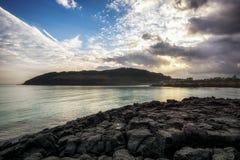 Sunrise over the black basalt. Sunrise view over the black basalt. Taken in Hamdeok Seoubong Beach in Jeju Island, South Korea Stock Photo