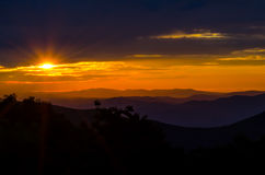 Sunrise Over the Blue Ridge. Sun rays peek through the clouds over a hazy purple mountain range stock images