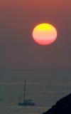 Sunrise over boat in ocean Stock Photo