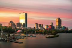 Sunrise over Boston city with boat and harbor royalty free stock image