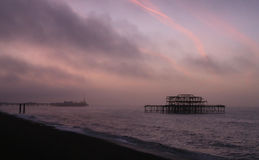 Sunrise over Brighton piers Stock Photos