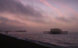 Sunrise over Brighton piers Stock Photos
