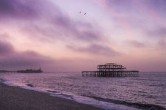 Sunrise over Brighton piers Stock Photo