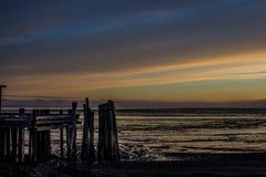 Sunrise over Bristol Bay from the dock at Ekuk Alaska at low tide. stock photos