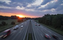 Sunrise over Busy German Motorway. Raising red sun over German motorway with multiple cars blurred in speed motion stock photo