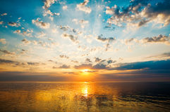 Sunrise over the calm waters of Gdansk bay. Beautiful sunrise with clouds, lightstreaks and golden water Royalty Free Stock Photo