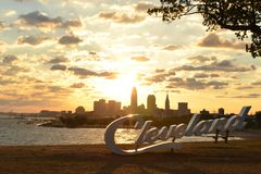 Sunrise over Cleveland sign and skyline at Lake Erie Edgewater park. Morning view of Cleveland skyline, Lake Erie, and paraglider from Edgewater park Royalty Free Stock Image