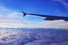 Sunrise over the clouds. A view from the aircraft window on wing, clouds, mountains and the Moon Stock Image