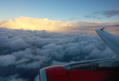 Sunrise over the clouds and airplane wing royalty free stock images