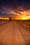 Sunrise Over A Colorado Dirt Road. A country dirt road leads travelers to a brilliant sunrise in Denver, Colorado Royalty Free Stock Photography