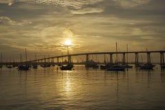 Sunrise over Coronado Bay, San Diego, California bathes everything in a warm golden light. View from Coronado Island towards the Coronado Bridge stock photos