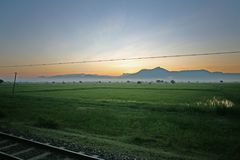 Sunrise over the countryside of central Myanmar on the Yangon to Mandalay sleeper train, Burma. Distant mountains seen from the sleeper car of the Yangon to Royalty Free Stock Image