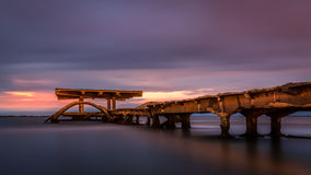 Sunrise over a decayed pier Stock Image