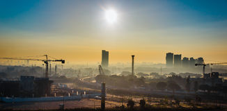 Sunrise over developing city, with cranes Royalty Free Stock Photos