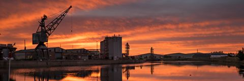 Panoramic sunrise over the docks at high tide. Vivid red sky as the sun rises over Boston docks at high tide Stock Images