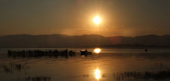 Sunrise  over Dojran Lake and fisherman between reeds Stock Photos