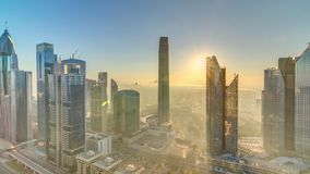 Sunrise over Dubai skyline in the morning, aerial top view to downtown city center landmarks timelapse.