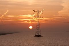 Sunrise over the Dutch sea with electricity pylons Royalty Free Stock Images