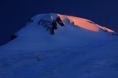 Sunrise over Elbrus Peak. First sun rays over Elbrus Peak (5642m), Caucasus Mountains, Kabardino-Balkaria Republic royalty free stock photo