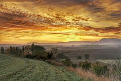 Sunrise over field in fall. Rural landscape of fields in autumn colors at sunrise Stock Photo