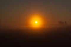 Sunrise over a field in the fog Royalty Free Stock Image