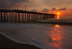 Sunrise over a fishing pier in North Carolina. Rays from the rising sun illuminate a fishing pier, the ocean and foam from a beach in Nags Head, North Carolina Stock Photo