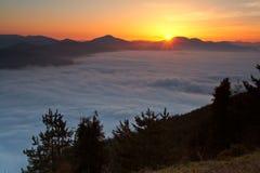 Sunrise over the fog stock photos