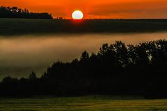 Sunrise over a foggy meadow. Wispy fog, Springbank, Alberta, Canada Stock Photos