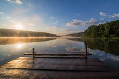 Sunrise over the foggy river with a wooden pier. Foggy summer sunrise over the river with a wooden pier royalty free stock image