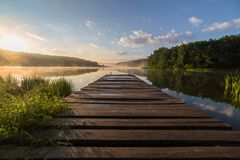 Sunrise over the foggy river with a wooden pier. Foggy summer sunrise over the river with a wooden pier royalty free stock photo